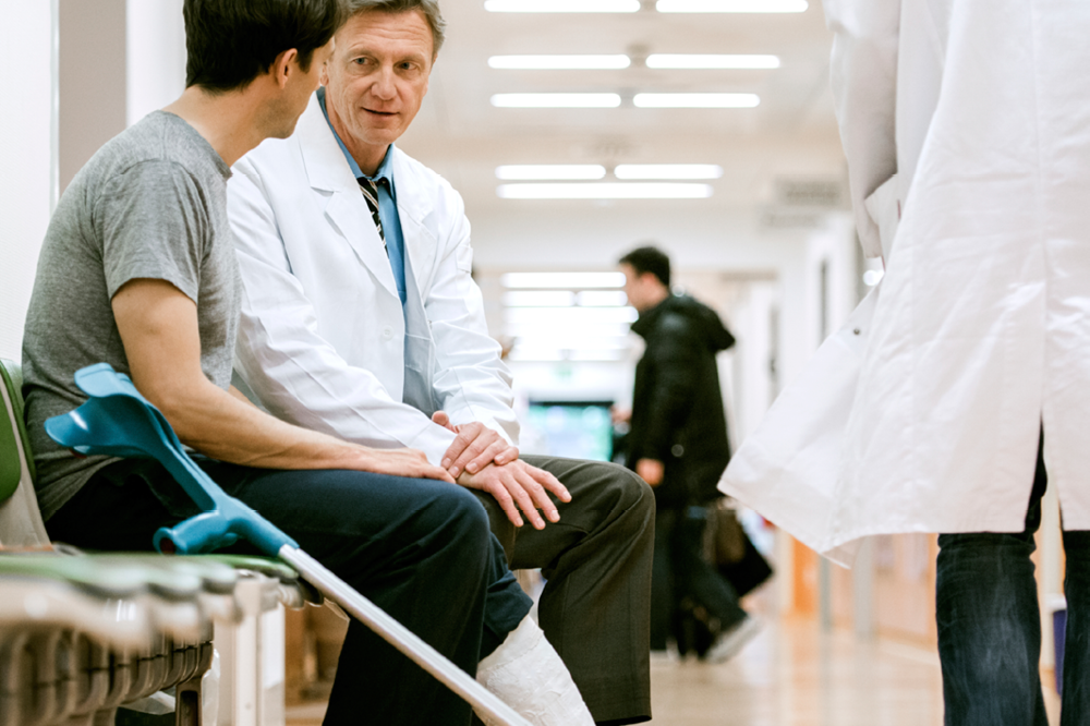 Man In A Cast Speaking With A Doctor