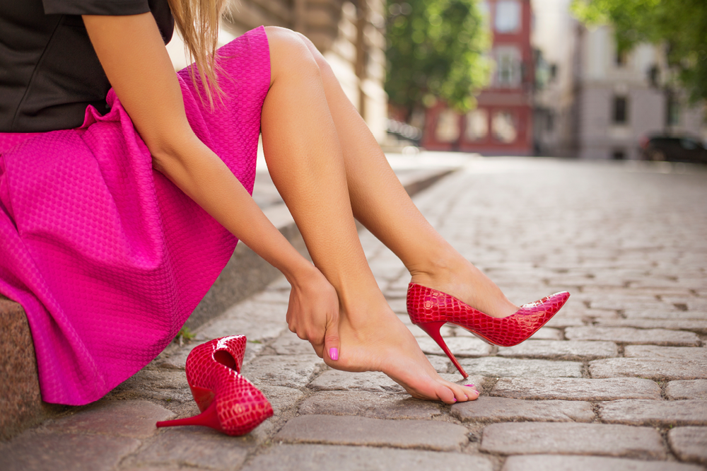 Woman In a Pink Skirt Holding Her Foot In Pain